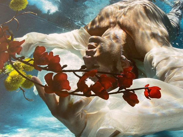 Cold Song - an underwater photograph of a man with flowers - by Alex Sher
